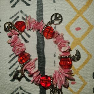 Hand-crafted bracelet, pink sea shells with red beads and embellished with charms.